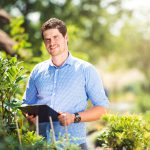 Gardener holding a clipboard, in his garden, green sunny nature